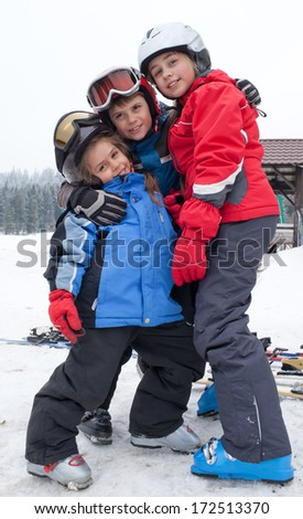 Three happy children in ski clothes with helmets and goggles after skiing