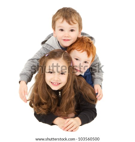 Three happy children laying down in pile. Isolated on white.