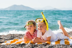 Three happy children on beach with colorful face masks and snorkels, sea in background. Summer vacation