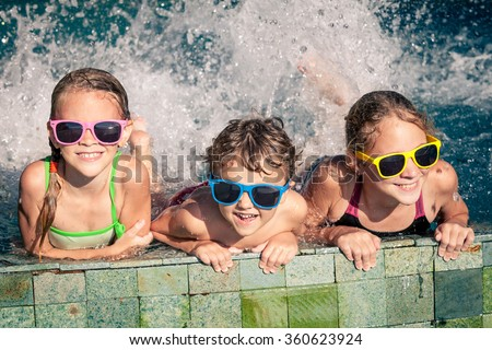 Three happy children  playing on the swimming pool at the day time. Concept of friendly family.