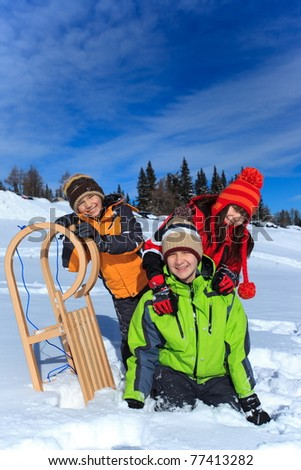 Three happy children playing with a sled in winter snow.