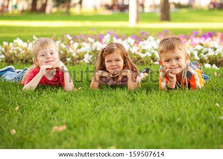 Three happy children, two boys and a girl lying on the grass on the lawn.
