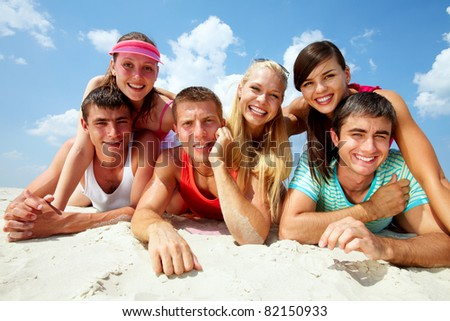 Three happy couples lying on sand and looking at camera