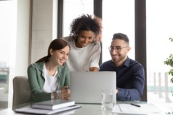 Three happy diverse colleagues working on project together, using laptop, sitting at table in office, discussing strategy, brainstorming, smiling African American businesswoman training staff