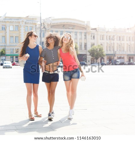 Three happy female multiethnic friends. Girls in colourful clothes having a walk in city in summer and having fun, copy space. Urban lifestyle, friendship concept