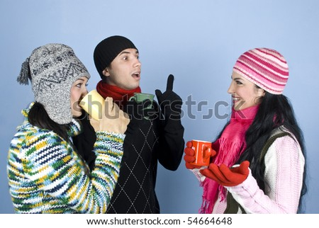 Three happy friends  in winter clothes with  sweaters,hats,scarves and gloves holding hot cup of tea  and drinking  ,laughing and having  a cheerful conversation