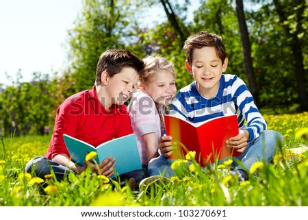Three happy friends reading on the lawn