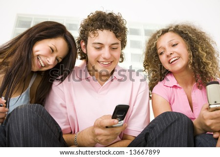 Three happy friends sitting and looking at mobilephone. A boy holding mobile phone. Low angle view.