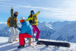 Three happy friends snowboarders and skiers are having fun on a ski slope with ski and snowboards in a sunny day and mountains view background.