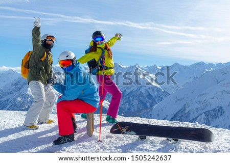 Three happy friends snowboarders and skiers are having fun on a ski slope with ski and snowboards in a sunny day and mountains view background. #1505242637