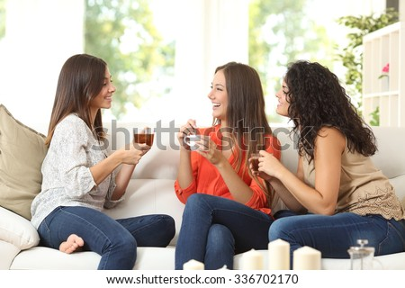 Shutterstock Three happy friends talking and drinking coffee and tea sitting on a couch at home