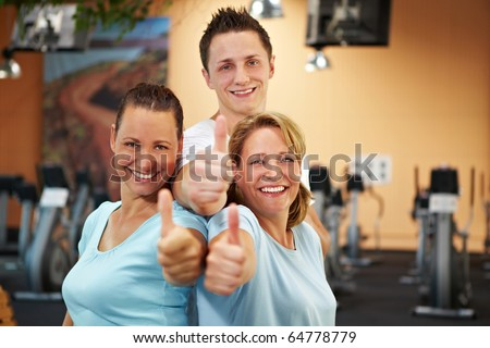 Three happy gym employees holding thumbs up