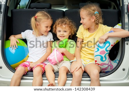 three happy kids in the car