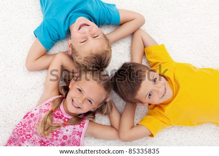 Three happy kids laying on the floor in circle laughing