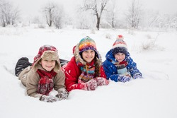 Three happy kids lying down together on snow, outdoors winter vacation