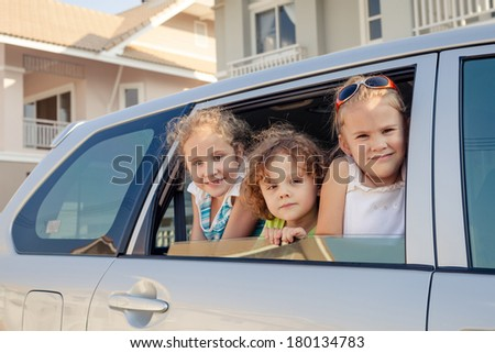 three happy kids sitting in the car