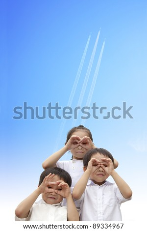three happy kids watching the aircraft flying through to sky - stock photo
