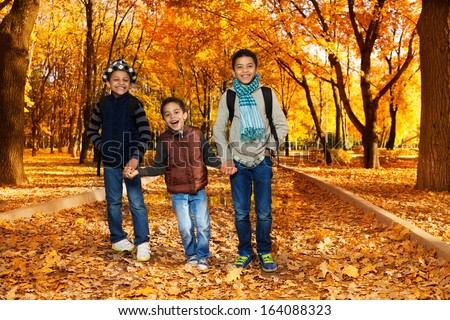 Three happy, laughing  boys, happy brothers 5-10 years old going together holding hands in the park wearing backpacks and autumn clothes in maple and oak park with lots of autumn orange leaves