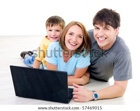 Three happy laughing people with little boy on the floor with laptop - indoors - stock photo