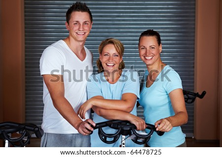 Three happy people standing around bikes in gym