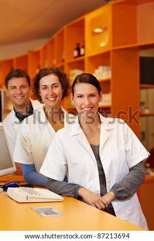 Three happy pharmacists at a counter in a pharmacy