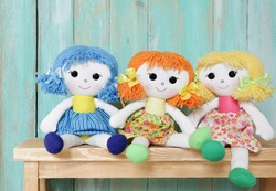 three happy rag dolls on wooden background