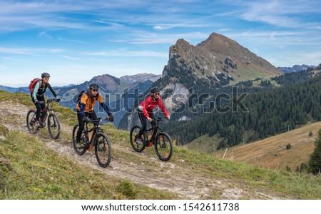 three happy senior adults, riding their mountain bikes in the autumnal atmosphere of the Bregenz Wald mountains near Mellau, Vorarlberg, Austria Stock foto ©
