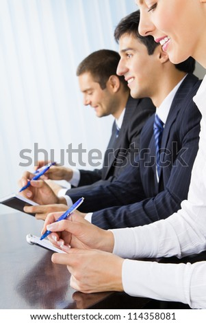Three happy smiling businesspeople at meeting, presentation or conference