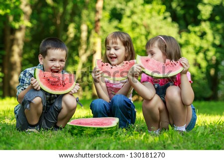 Three happy smiling child eating watermelon in park