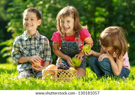 Three happy smiling child playing in park with fruits
