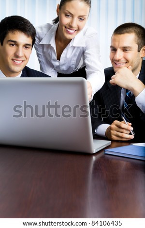 Three happy smiling successful business people working with laptop at office