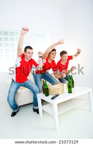 Three happy sport's fans get up from couch with raised hands.