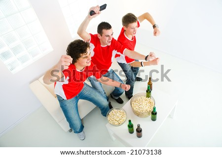 Three happy sport's fans get up from couch with raised hands. High angle view.