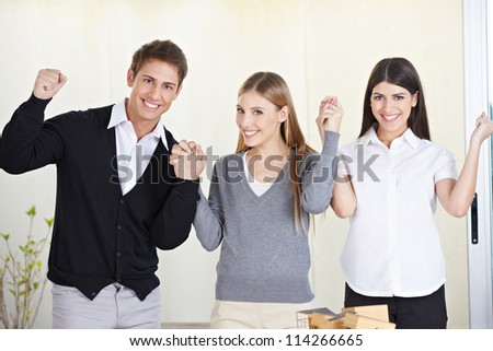 Three happy students holding their hands and cheering in university