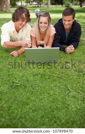 Three happy students in a park lying while using a laptop
