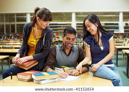 Three happy students learning in university library - stock photo