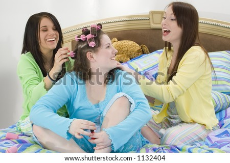 stock photo : Three happy teen girls at slumber party doing hair and ...