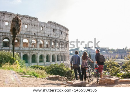 Three happy young friends tourists with bikes at Colosseum in Rome having fun #1455304385