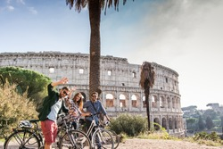 Three happy young friends tourists with bikes at Colosseum in Rome having fun posing and waving at camera