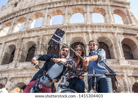 Three happy young friends tourists with bikes at Colosseum in Rome taking pictures and selfies with smartphone