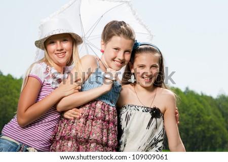 three happy young girl friends under umbrella - stock photo