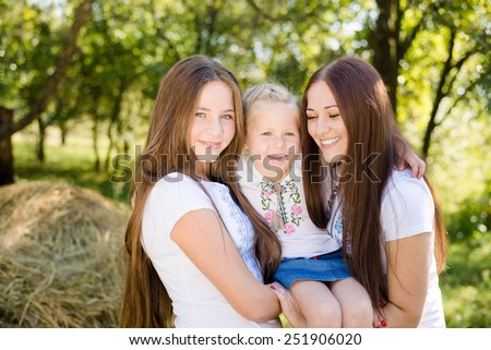 Three happy young ladies having fun embracing on outdoors copy space background