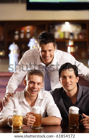 Three happy young men in the bar