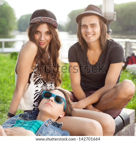 Three Happy Young People Sitting Together On Park Bench. Outdoors