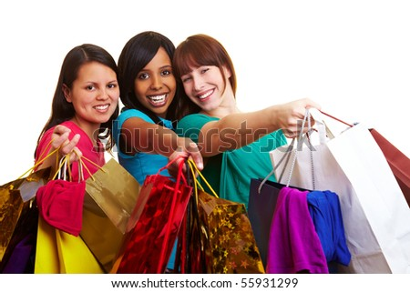Three happy young women with many colorful shopping bags