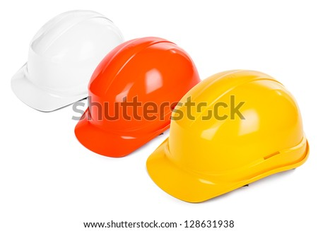 three hard hats on white background, focus set on the yellow one