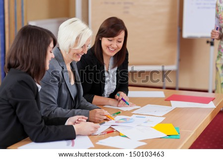 Three hardworking female business colleagues having a meeting sitting at a table together discussing paperwork and graphs