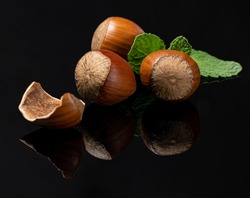 Three Hazelnuts on a black backdrop with mint leafes and reflection