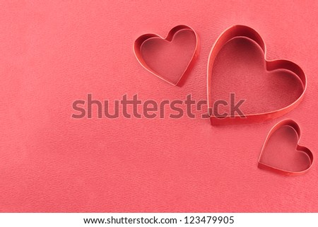 Three heart shaped cookie cutters over a red background.