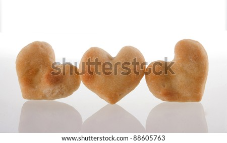 Three heart-shaped cookies isolated and its reflection on white background.  Included clipping path, so you can easily cut it out and place over the top of a design.